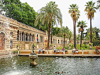 Tourists resting around a fountain in Royal Gardens, Alcazar,  Séville, Spain.