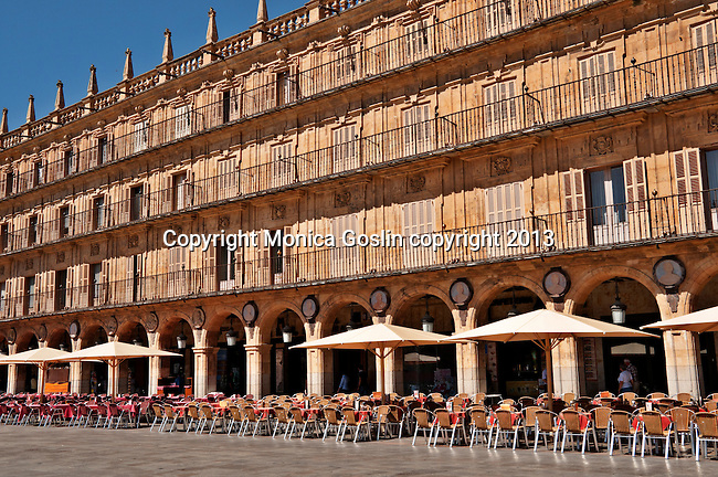 Red tables of one of the many cafes that line Plaza Mayor which is said to be the most beautiful plaza in Europe