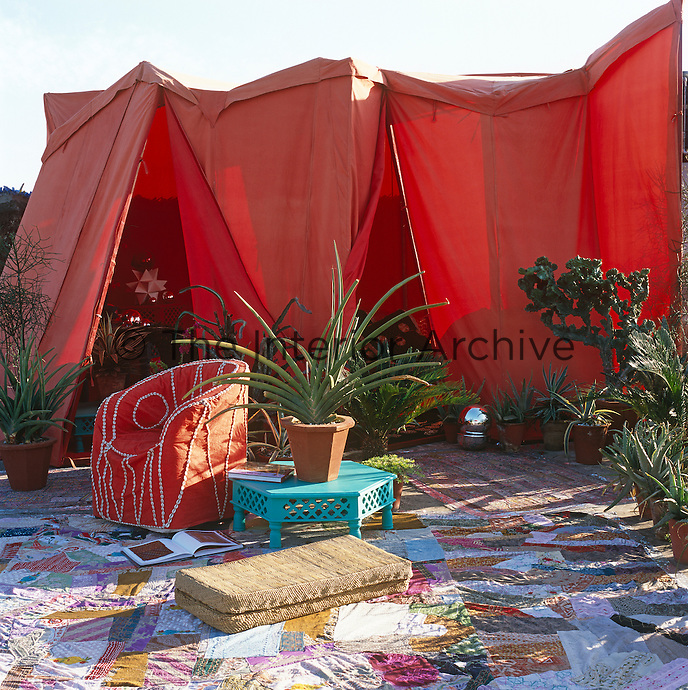 A rooftop red canvas tent opens onto a cactus-filled garden