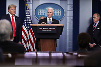 United States Vice President Mike Pence, right, speaks as US President Donald J. Trump, left, listens during a press conference with members of the coronavirus task force in the Brady Press Briefing Room of the White House on March 24, 2020 in Washington, DC.  Standing at far right is Director of the National Economic Council Larry Kudlow.<br /> Credit: Oliver Contreras / Pool via CNP/AdMedia