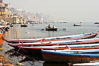 A few boats moored on ghats waiting for tourists while another boatman takes pilgrims on a tour of  Ganges River on a misty morning. (Photo by Matt Considine - Images of Asia Collection)