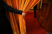 A security officer holds open a curtain during the opening session of the National People's Congress (NPC) at the Great Hall of the People, in Beijing, China, March 5, 2016. REUTERS/Damir Sagolj