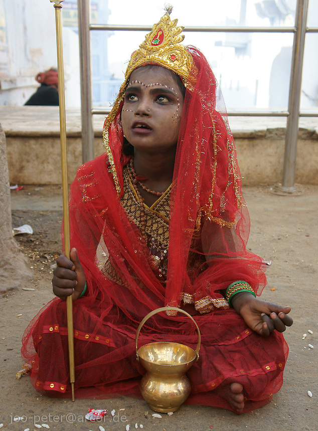 child dressed up as god waiting for donations in the streets of holy city Pushkar, Rajastan, India