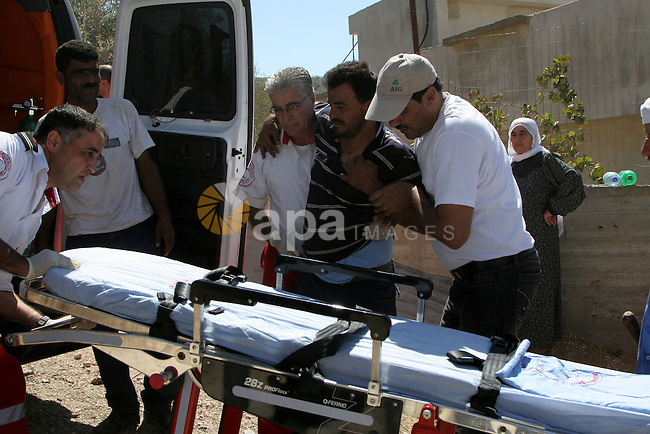 Palestinian medical workers carrying a Palestinian farmer who was wounded after scuffles with Israeli settlers , in the village of Burin, near Nablus in the West Bank , Monday, Sept. 20,2010 . Palestinian farmers said the Israelis settlers from the settlement on Yizhar  attack  farmers and wounded one of the farmers. Photo by Wagdi Eshtayah