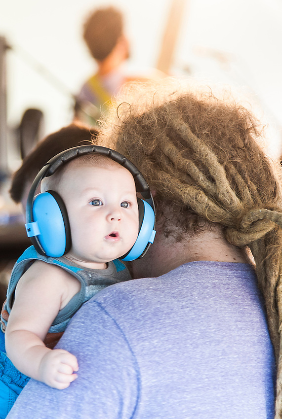 A young boy wears headphones while his father works backstage during Blissfest music festival in Michigan.