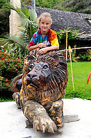 8 year old child on carving of lion. Crouching Lion Inn, Kamehameha Hwy. Kaaawa, Oahu