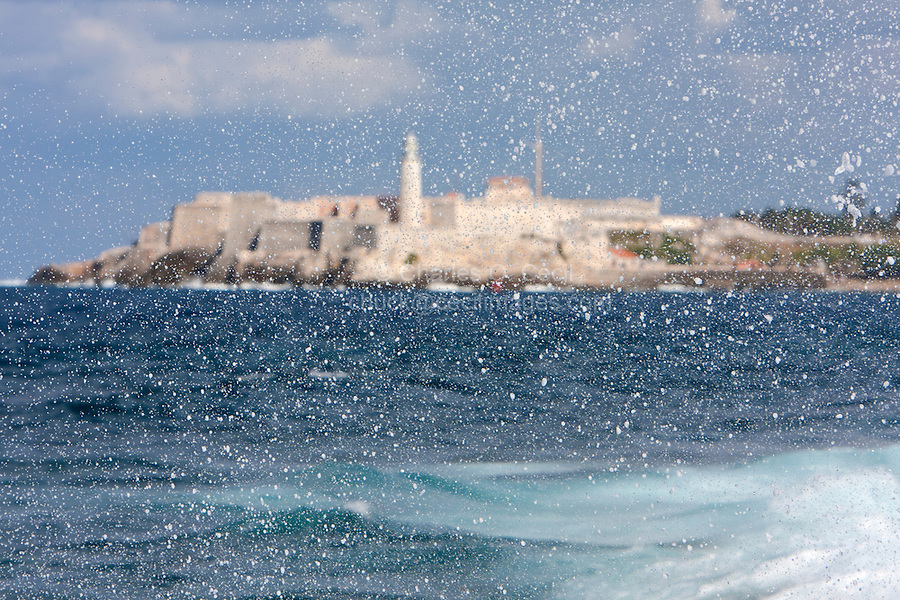 Cuba, Havana.  Waves splash on the Malecon sea wall.  In the background the Castillo del Morro (El Morro Fortress), Guards the Entrance to Havana Bay.  Construction was begun in 1589.  Today's lighthouse was built in 1845.