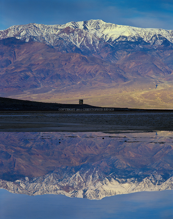 An RV driver stops to take in the view just south of Badwater of the Panamint Mountains sprinkled with snow from a clearing winter storm. Average annual precipitation is 1.58 inches (40 mm). Death Valley National Monument Est. February 11, 1933; Death Valley National Park in 1994. 5,270 square miles (13,649 km2). Inyo County, CA.