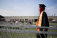 Graduate Haadiya Muhammad walks a platform to receive her diploma, Friday, July 17, 2020 during a graduation ceremony at Bentonville High School in Bentonville. Check out nwaonline.com/200718Daily/ for today's photo gallery. <br /> (NWA Democrat-Gazette/Charlie Kaijo)