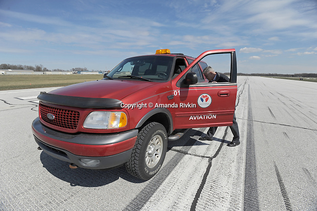 """Airport Manager Andy Jones enters his beacon-lit airport vehicle on the runway at the Elkhart Municipal Airport in Elkhart, Indiana on April 8, 2009.  As part of the """"bail out"""" funds, one of two runways will be repaired; Jones said he had to turn down the request from Air Force One and the president's advance staff, citing the weight of the aircraft and the fragile state of the runways, to land at Elkhart International Airport."""