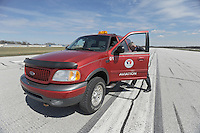"Airport Manager Andy Jones enters his beacon-lit airport vehicle on the runway at the Elkhart Municipal Airport in Elkhart, Indiana on April 8, 2009.  As part of the ""bail out"" funds, one of two runways will be repaired; Jones said he had to turn down the request from Air Force One and the president's advance staff, citing the weight of the aircraft and the fragile state of the runways, to land at Elkhart International Airport."