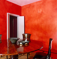 The walls of the dining room glow vermilion and have been left free from decoration