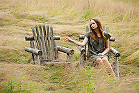 Young woman sitting in field next to empty adirondack chair