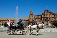 Horsedrawn cart driving people around the Plaza de Espana during the Feria De Abril, Seville, Andalusia, Spain.