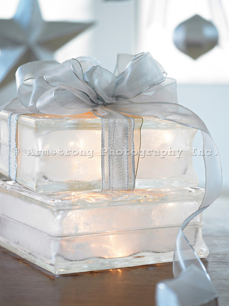 Silver winter holiday decorations with decorative illuminated gift box in foreground