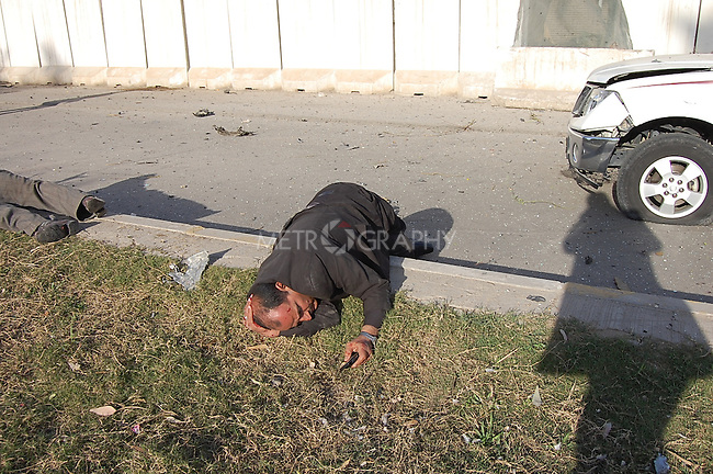 BAGHDAD, IRAQ:  A wounded man lies on the ground after an explosion outside the Sheraton Hotel, January 25, 2010...At least 36 people have died in three large explosions apparently targeting hotels in the heart of Iraq's capital..More than 70 people were injured in the Baghdad blasts, which officials said were caused by suicide car bombers.  They struck near the Sheraton, Babylon and Hamra hotels, which are popular with Western businessmen and media....Photo by Qeas Kazm/Metrography