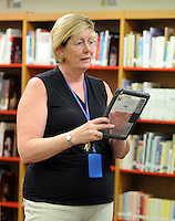 Kathy Christie instructs students on how to place a case on their iPads after the Neshaminy Maple Point Middle School students arrived back from the Apple Store Monday August 17, 2015 in Middletown, Pennsylvania. The students will serve as IT ambassadors while helping their classmates and teachers navigate iPad issues this school year. (Photo by William Thomas Cain)
