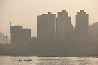 Daytime landscape view of a small river boat on the Cháng Jiāng with commercial buildings in the background in the Wànzhōu District in the Chongqing Municipality.  © LAN