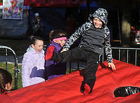 NWA Democrat-Gazette/MICHAEL WOODS • <br /> Kate Kifer, 7, (from left and Claire Wilhelm, 8, watch as Will Storms, 7, gets bounced into the air in the Kids Zone Saturday November 21. 2015 while tailgating before the start of the Arkansas football game.
