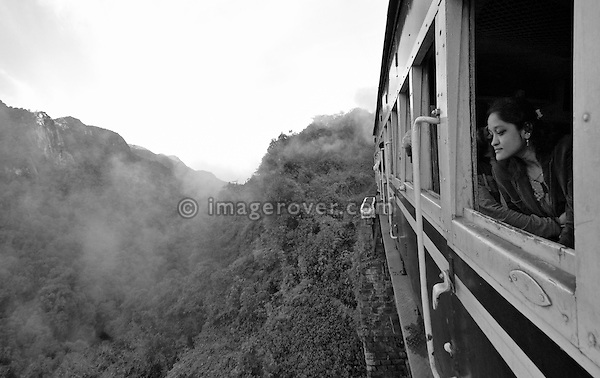 Indian woman travelling in the Nilgiri Mountain Railway. Looking out of the window while the steam train is crossing one of the many bridges between Coonoor and Metapulayam. Part of the journey is managed only by a rack-and-pinion system. India, Tamil Nadu. --- Info: The Nilgiri Mountain Railway (NMR) is the only rack railway in India and connects the town of Mettupalayam with the hill station of Udagamandalam (Ooty), in the Nilgiri Hills of southern India. The construction of the 46km long meter-gauge singletrack railway in Tamil Nadu State was first proposed in 1854, but due to the difficulty of the mountainous location, the work only started in 1891 and was completed in 1908. This railway, scaling an elevation of 326m to 2,203m and still in use today, represented the latest technology of the time. In July, UNESCO added the NMR as an extension to the World Heritage Site of Darjeeling Himalayan Railway.