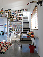 In the study, which is like an air-lock between the first floor rooms, a collection of family photographs adorns one wall. A classic Eames chair, a plain desk and a simple rug are the sparse furnishings. The stairs lead up to the roof terrace.