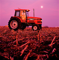 A farmer works into the moonlit evening as he drives a new tractor through a field of corn stubble. Missouri.