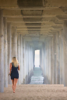 Woman walking Under The Huntington Beach Pier Orange County, California