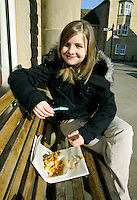 Teenage girl eats traditional English fish and chips meal on a bench in the Derbyshire village of Bakewell