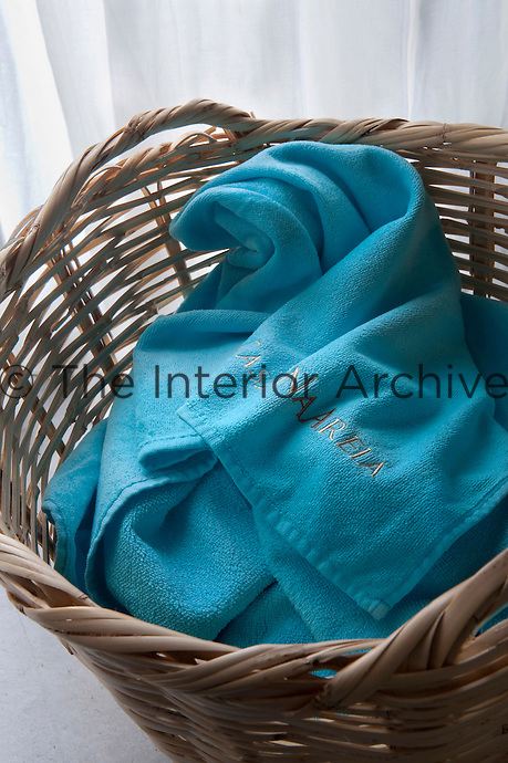 A simple wicker basket in the contemporary bathroom contains a towel embossed with the name CasasNaAreia