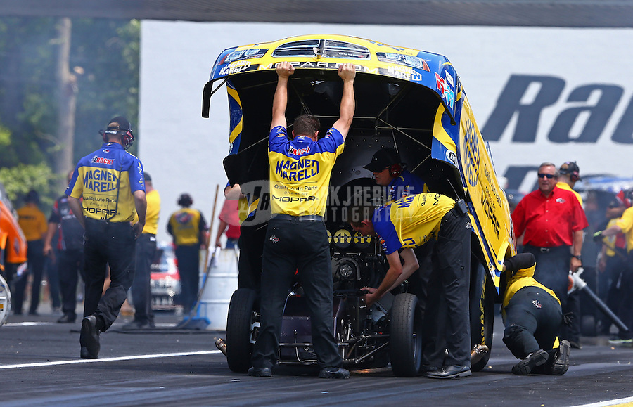 Jun. 2, 2013; Englishtown, NJ, USA: Crew members work under the body of NHRA funny car driver Matt Hagan during the Summer Nationals at Raceway Park. Mandatory Credit: Mark J. Rebilas-