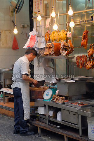 Hong Kong, China, Asia. Hong Kong Kowloon. Butcher with large knife at work.