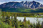 Old log cabin along Nenana River along Denali Highway. Alaska Range is in the background. Southcentral Alaska, Summer.
