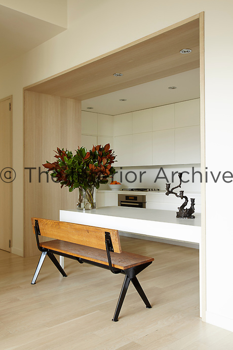 A contemporary kitchen is housed in an alcove off the living area and furnished with a Jean Prouve bench