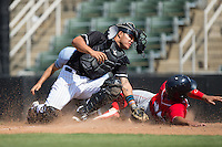 Wilson Garcia (25) of the Lakewood BlueClaws is tagged out at home plate by Kannapolis Intimidators catcher Daniel Gonzalez (8) at Kannapolis Intimidators Stadium on May 8, 2016 in Kannapolis, North Carolina.  The Intimidators defeated the BlueClaws 3-2.  (Brian Westerholt/Four Seam Images)