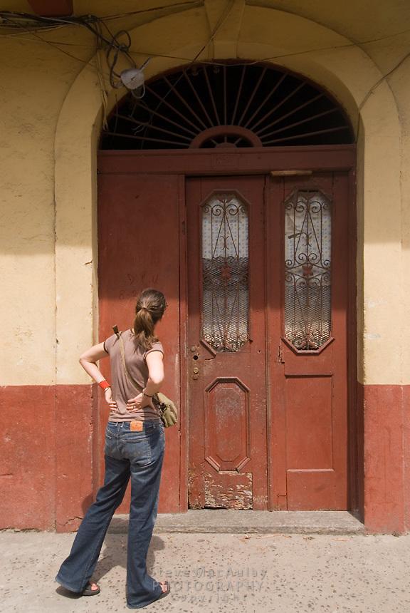 Woman checks out old doorway, Casco Viejo, Panama City, Panama
