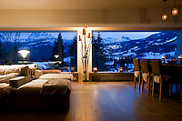 The open plan living room has stunning evening views of the surrounding mountains through a pair of large picture windows