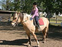 Mädchen beim Reitunterricht auf Ponyhof, Mädchen mit ihrem Reitpony auf dem Reitplatz, Reiten, Reiterhof, Gestüt