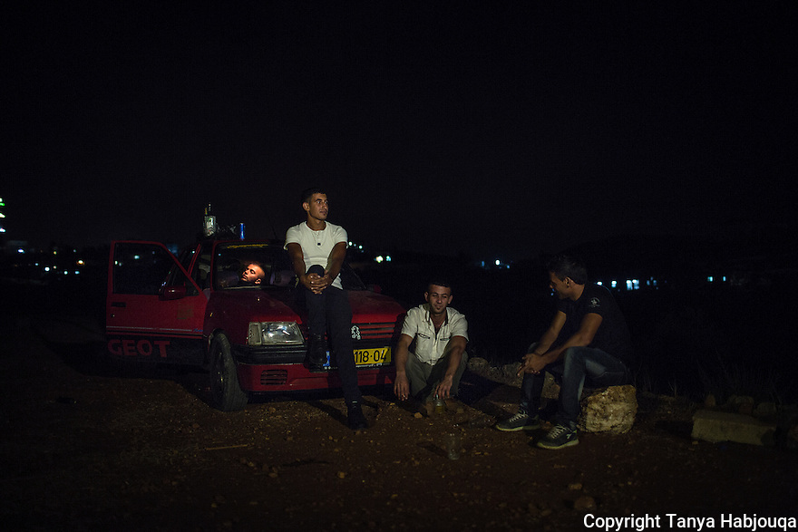 Youth enjoy some vodka and conversation on the outskirts of Kufr Ni`ma village in the West Bank.