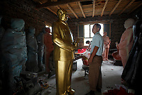 "A workers looks up at a statue of Mao Zedong at the workshop of a ""Red"" memorabilia collector and manufacturer, near Mao's birthplace in Shaoshan, Hunan Province, China on 12 August 2009.  The workers were once electricians."