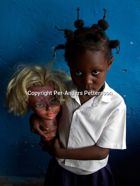 dicocon00138 .Country Congo Dorcas Otsudi, age 5, with a doll in her kindergarten classroom, at La Bambiniere School in Lingwala district on February 28, 2002 in Kinshasa, Congo. The teacher has given the children different toys to play with and she plays with the doll. She wants to be a housewife when she grows up..©Per-Anders Pettersson/iAfrika Photos