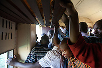 Passengers anticpate the final stop on the crowded train from Athi River to Nairobi.