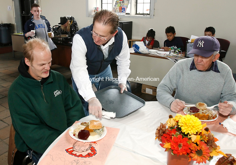 WATERBURY, CT, 11/27/08- 112708BZ06- David LaManna, of the United Methodist Church of Woodbury, serves a Thanksgiving Day meal to Gordon Rochon, of Waterbury, as Bill Drew, of Waterbury looks on at the Greater Waterbury Interfaith Ministries soup kitchen inside St. John's Church in Waterbury Thursday.<br /> Jamison C. Bazinet Republican-American