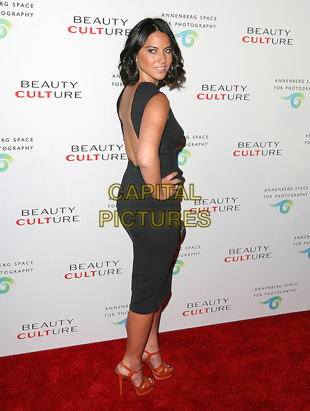 OLIVIA MUNN .at The opening of Beauty Culture - a photographic exploration of how feminine beauty is defined, challenged and revered in modern society held at Annenberg Space for Photography in Century City, California, USA,  .May 19th 11..full length dress hand on hip clutch bag sleeveless black orange platform ysl tribute shoes sandals   back over shoulder rear behind                                   .CAP/RKE/DVS.©DVS/RockinExposures/Capital Pictures.