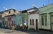 Cachoeira, Brazil. Typical rural town cobbled street with colonial style houses, mules and donkeys with pannier baskets, satellite television dishes on the roofs. Bahia State.