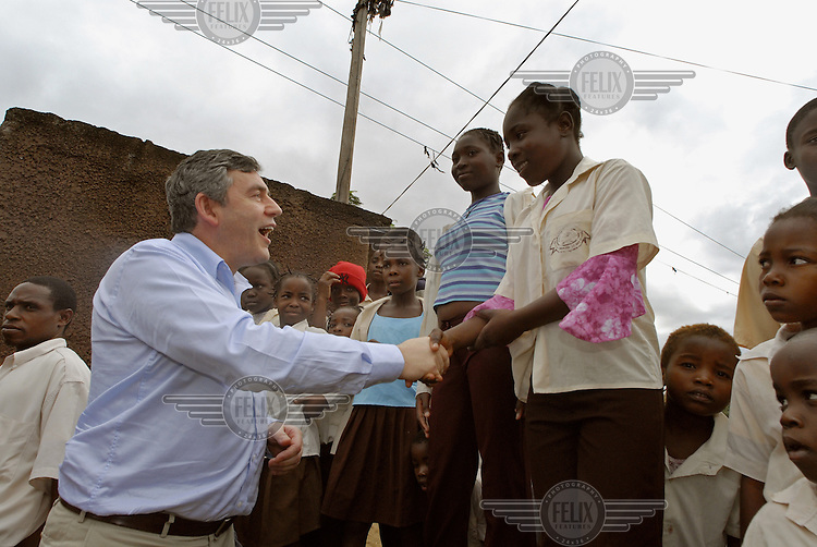 Pupils at Forces primary school urge Gordon Brown, British Chancellor of the Exchequer, to support the 'Every child needs a teacher' campaign.  Brown was in Mozambique to launch a new 'Free education for all' initiative.
