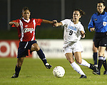 Tiffany Roberts and Kacey White (9) fight for the ball at SAS Stadium in Cary, North Carolina on 3/22/03 during a game between the Carolina Courage and University of North Carolina Tarheels. Referee Rachel Woo watches.