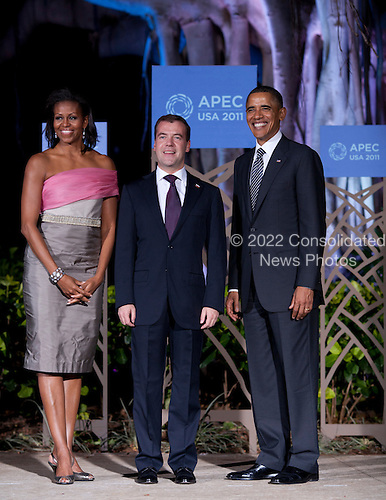 United States President Barack Obama (R) and First Lady Michelle Obama (L) greet President Dmitry Medvedev of Russia (C) before the Asia-Pacific Economic Cooperation (APEC) summit dinner at the Hale Koa Hotel in Honolulu, Hawaii on Saturday, November 12, 2011..Credit: Kent Nishimura / Pool via CNP