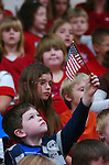 A boy holds his American flag high during a Veterans Day ceremony at  Ashkar Elementary School.