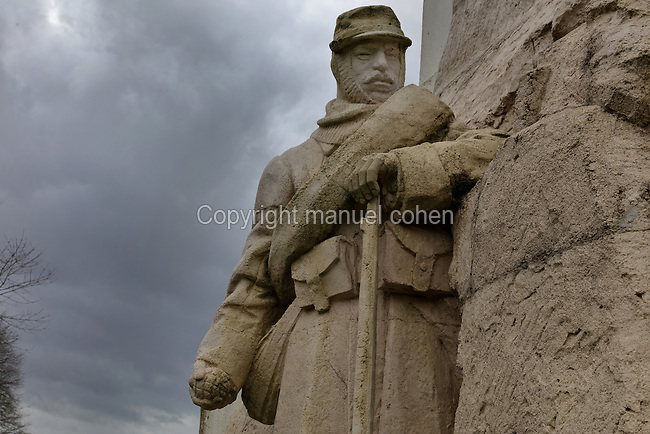 Sculpture of a French infantryman with a grenade and rifle, on the Monument to the soldiers who fought and died at the Battle of Vauquois, built 1926 on the site of the old town hall, on the French side of the Butte de Vauquois, 25km West of Verdun, Meuse, Lorraine, France, site of the Battle of Vauquois, 1915-18, in World War One. The monument was designed by Monestier and built by the sculptor Roussel. It is an obelisk in the shape of a lantern of the dead, with sculptures on an armed French soldier, a mutilated tree (a marker for French soldiers) and a tunneler. Picture by Manuel Cohen
