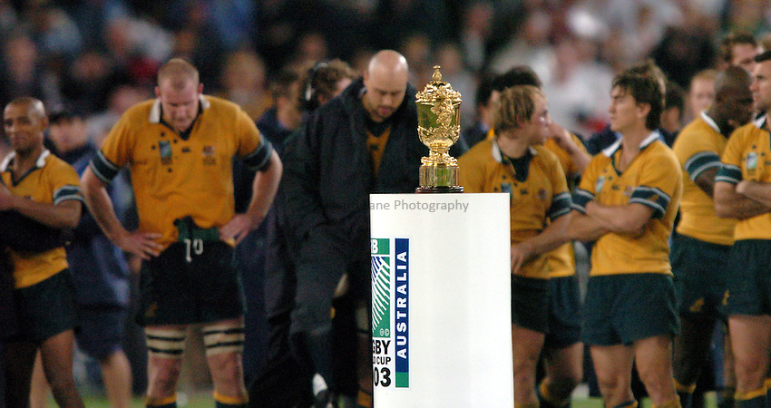 Photo: Richard Lane..Australia v England. Rugby World Cup Final, at the Telstra Stadium, Sydney. RWC 2003. 22/11/2003. .The Australian team look dejected behind the William Webb-Ellis Trophy.